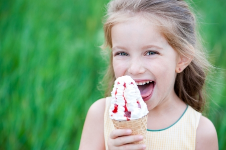 girl licking: Beautiful little girl eats ice-cream in the summer