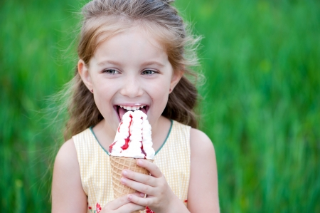 lick: Beautiful little girl eats ice-cream in the summer
