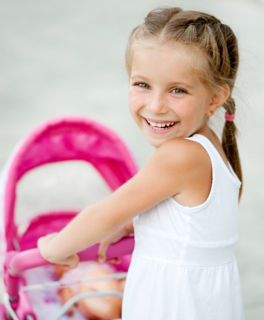 Cute little girl with her toy carriage photo