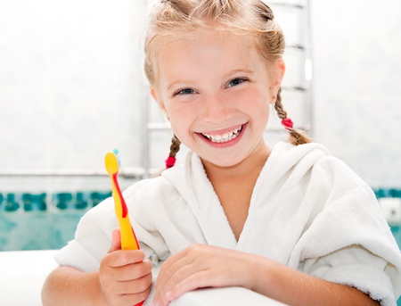 Little girl brushing teeth in bath photo