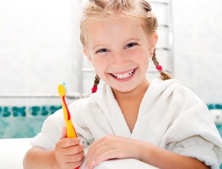 little girl bath: Little girl brushing teeth in bath Stock Photo
