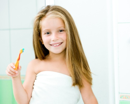 reflection in the mirror of a little girl with toothbrush photo