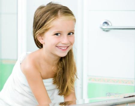 personas tomando agua: Ni�a linda lavado en ba�o de reflexi�n en el espejo
