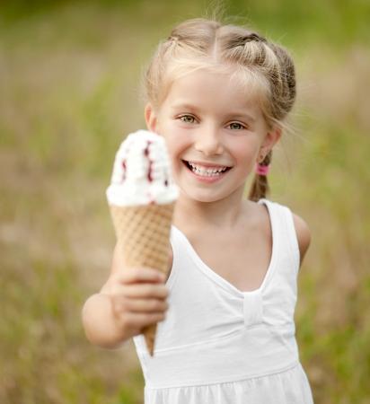 strawberry ice cream: Beautiful little girl eats ice-cream in the summer