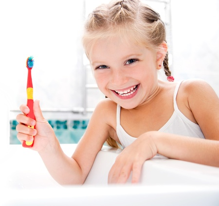 oral care: Little girl brushing teeth in bath Stock Photo