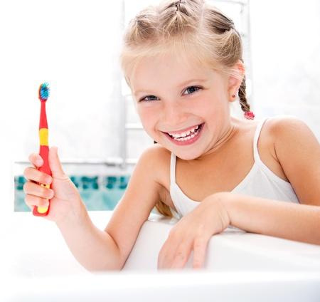 higiene bucal: Ni�a cepill�ndose los dientes en el ba�o Foto de archivo