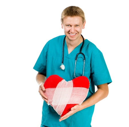 Male doctor with a heart in his hands and stethoscope on a white background Stock Photo - 16036258