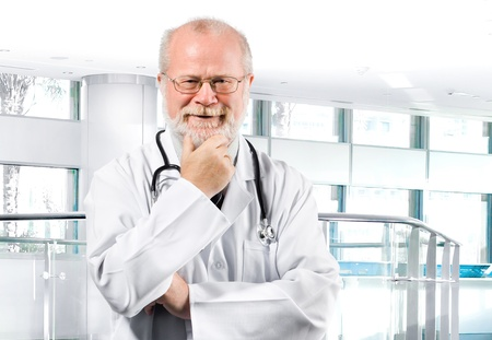 Portrait of pensive senior medical doctor isolated over clinic background photo