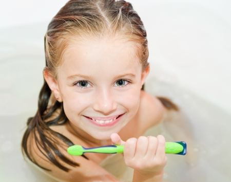 Cute girl brushing teeth in bath photo