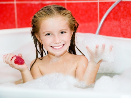 bathwater: Cute little girl in the bath with a red soap