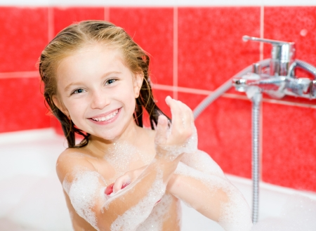 Cute girl in the bath with a red soap Stock Photo