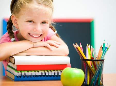 kids class: Portrait of smart girl at workplace with the books Stock Photo