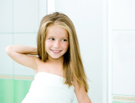 Cute little girl washing in bath photo