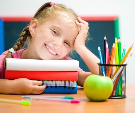 niños dibujando: Retrato de niña linda en el lugar de trabajo con los libros