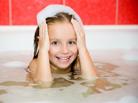 bathwater: Small pretty girl is taking a bath with a foam Stock Photo