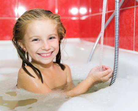 Cute little girl is taking a bath with a foam photo