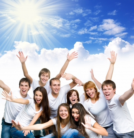 young smiling people over blue sky photo
