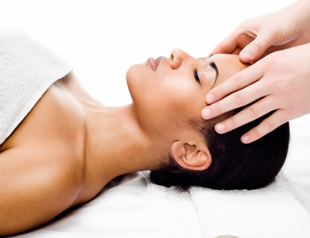 face massage: Beautiful young woman receiving facial massage with closed eyes in a spa salon