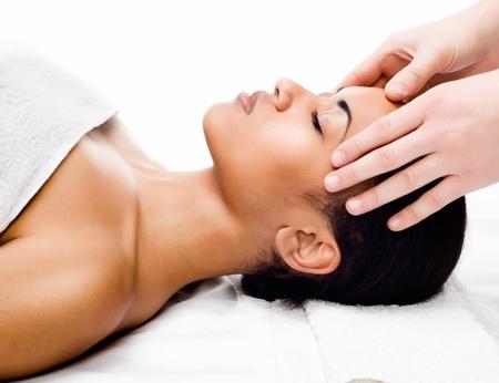 masajes relajacion: Mujer hermosa joven que recibe masaje facial con los ojos cerrados en un sal�n de spa Foto de archivo