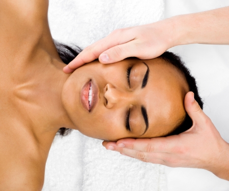 head massage: Beautiful young woman receiving facial massage with closed eyes in a spa center