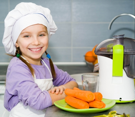 girl making fresh and healthy juice with a juice extractor photo