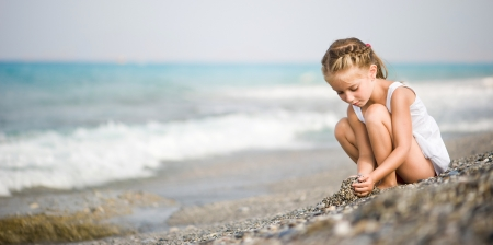 builds: girl builds a house of pebbles on the beach
