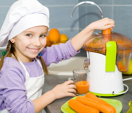 little girl making fresh carrot juice with a juice extractor photo