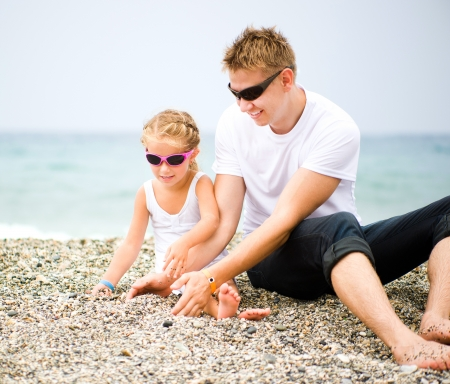 father play with his daughter on the beach photo