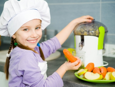 smily cute girl making fresh apple juice with a juice extractor photo