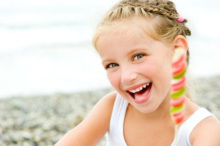 smily kleines Mädchen mit einem Bonbon auf tropischen Strandurlaub