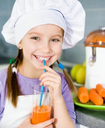 Sonriente niña bebe un jugo de zanahoria fresco Foto de archivo - 17385826