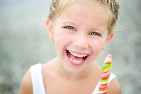 little girl beach: Adorable little girl with a colorful candy on tropical beach vacation