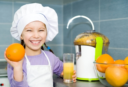 girl making fresh orange juice with a juice extractor photo