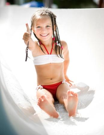 rutsche: Kleines M�dchen auf Wasserrutsche im Aquapark zeigen den Daumen