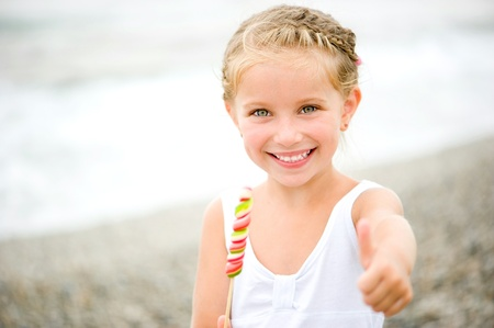 young female: Adorable little girl with a candy on show the thumb