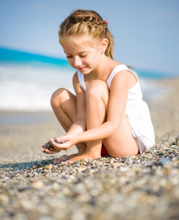 Seated girl with pebbles in her hands on the beach photo