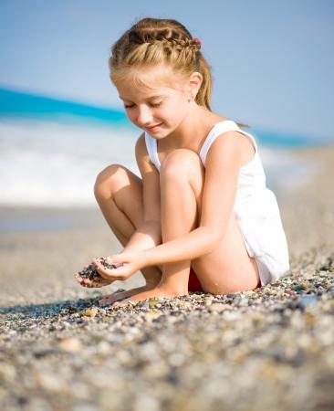 klein meisje op strand: Zittend meisje met steentjes in haar handen op het strand