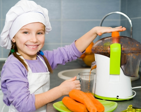 extractor: girl making fresh carrot juice with a juice extractor