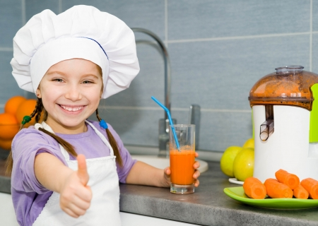 cute little girl with a fresh carrot juice show thumb photo