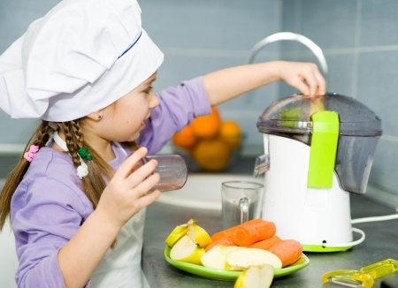 girl making fresh apple juice with a juice extractor photo