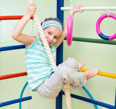 gymnastics equipment: happy little girl doing sports gymnastics at home gym Stock Photo