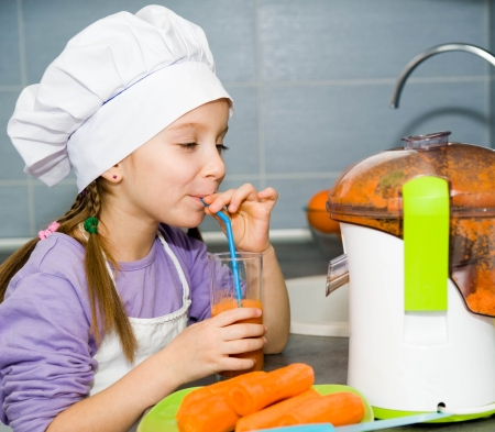 cute little girl drink a fresh carrot juice photo