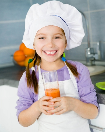smily little girl with a fresh carrot juice photo
