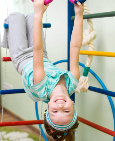 six year old girl playing at gymnastic rings photo