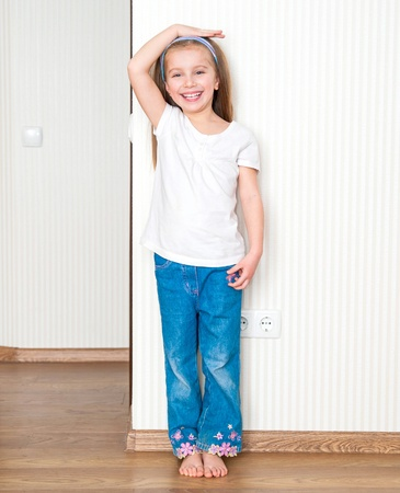 little girl measures the growth near the wall photo