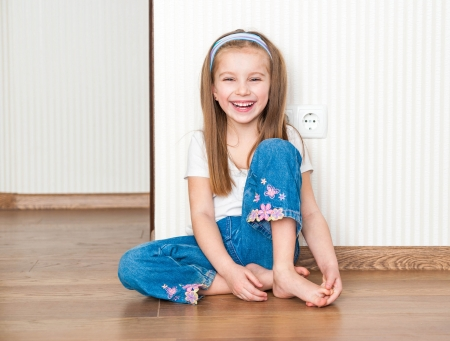 little girl siting on the floor at home photo