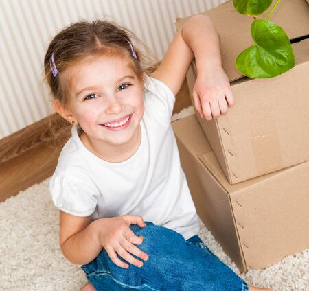 relocate: Little girl siting near cardboard box and plant