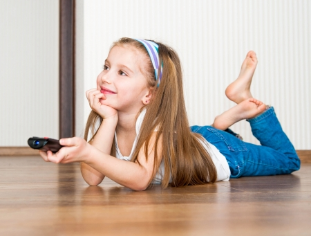 sitting on floor: little girl holding a remote control Stock Photo