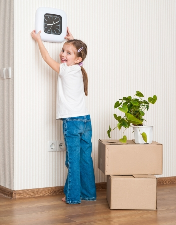 hangs: Little girl moving into new house  Hangs on a wall watch Stock Photo