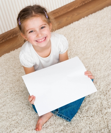 little girl sitting on the floor with the paper
